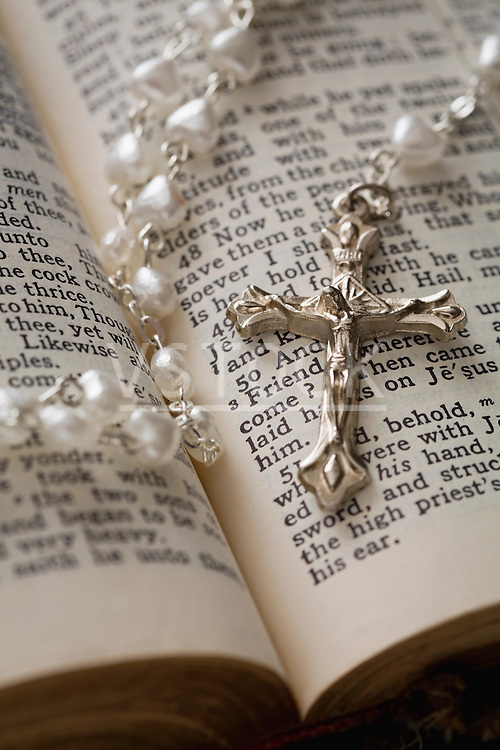 Close-up of open Bible and pearl rosary beads