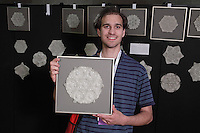 Benjamin Parker holds one of his tessellation designs in his Etched in Stone series on display at the OrigamiUSA 2013 Convention in New York.