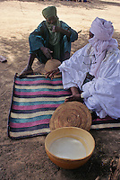 Akadaney, Central Niger, West Africa.  Fulani Nomads.  Two Men Talking.  Calabash of Camel's Milk in Foreground.