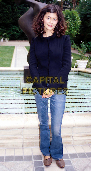 AUDREY TAUTOU..Ref:11355..french, long curly wavy hair, jeans, outside, outdoors, garden, black shirt, sculpture, swimming pool, black top, full length, full-length..www.capitalpictures.com..sales@capitalpictures.com..©Capital Pictures