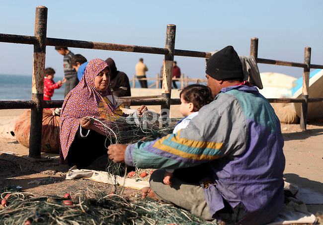 A Palestinian fisherman with his wife fix a fishing nets at the beach, in al-Shati refugee camp in Gaza city on January 20, 2013. Photo by Majdi Fathi