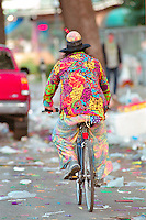 A colorfully dressed Mardi Gras reveller pedals down the littered St. Charles Avenue on February 14, 2002, after the Endymion float has passed, signifying the end of Mardi Gras.