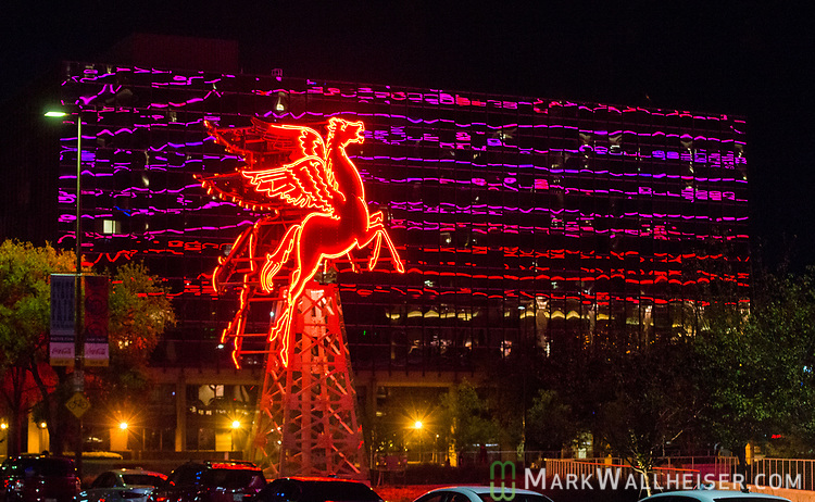 The historic Pegasus, or the flying red horse, that once graced the highest building in Dallas from 1934 till 1999 was found, restored and now sits in front of the Dallas Omni Hotel in downtown Dallas, TX.  The neon lights of the Omni are reflected in the building behind the Pegasus