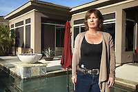"USA. Arizona state. Scottsdale. Carrie Lightfoot is the founder and CEO of ""The Well Armed Woman. Where the Feminine and Firearms Meet"" which sell online resources for women gun owners. She stands on her home's terrace near the swimming pool. In her belt's holster a SIG SAUER P238 .380 Auto Pistol as concealed carry firearm. The single-action pistol has a extended 7-round magazine capacity. Concealed carry or carrying a concealed weapon (CCW), is the practice of carrying a weapon (such as a handgun) in public in a concealed manner, either on one's person or in close proximity. A firearm is a portable gun, being a barreled weapon that launches one or more projectiles often driven by the action of an explosive force. Most modern firearms have rifled barrels to impart spin to the projectile for improved flight stability. The word firearms usually is used in a sense restricted to small arms (weapons that can be carried by a single person). The right to keep and bear arms is a fundamental right protected in the United States by the Second Amendment of the Bill of Rights in the Constitution of the United States of America and in the state constitutions of Arizona and 43 other states. 28.01.16 © 2016 Didier Ruef"