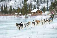 Musher Kelly Griffin crosses overflow on Ptarmigan creek near mile 101 checkpoint during the 1000 mile Yukon Quest sled dog race 2006, between Fairbanks, Alaska and Whitehorse, Yukon. Dubbed the toughest dogsled race in the world.