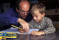 Bambino con il padre che lo aiuta a fare i compiti.Child with his father helping him to do his homework