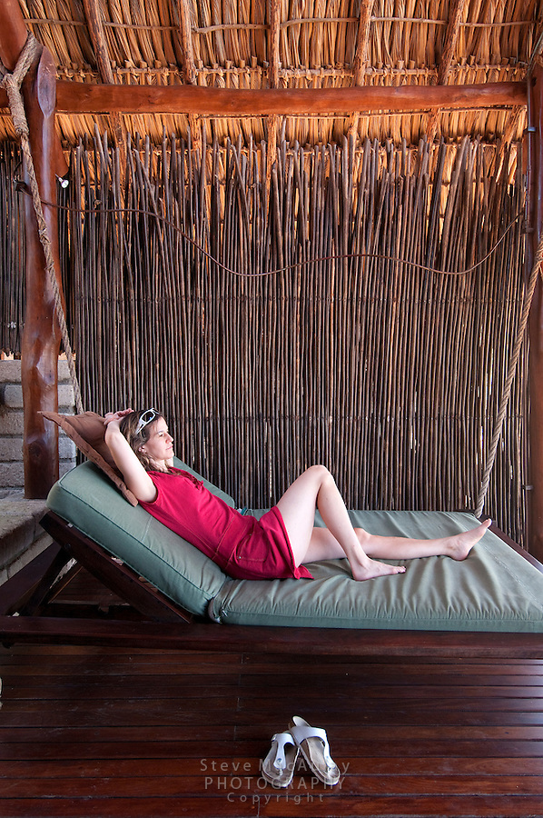 Young woman in red dress relaxing on large swinging lounge/bed, Morgan's Rock Hacienda and Eco Lodge, Nicaragua
