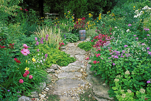 Path in garden with painted Mexican ceramic vase and blooming flowers, Missouri USA