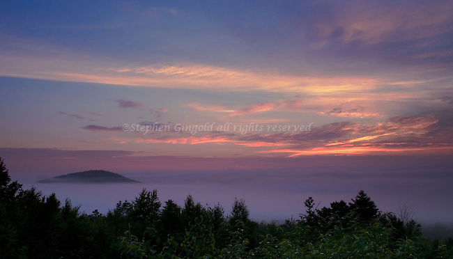 As the sun rises, it colors the valley fog over North Quabbin in central Masachusetts.