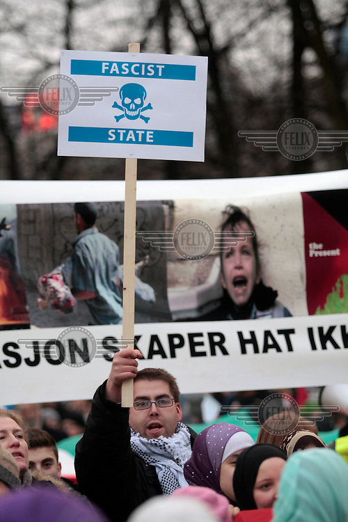 Protester with sign proclaiming Israel to be a fascist state. Pro-Palestinian protesters clashed with police as they held another demonstration against Israel in the Norwegian capital Oslo. Violent clashes lasted for hours  in the centre of Oslo. Israeli forces began a series of air strikes on the Gaza Strip on the 27th of December in retaliation against Hamas rockets fired into Israel. After eight days of bombardment, leaving over 400 Palestinians and four Israelis dead, Israeli tanks launched a ground invasion on the 4th of January.