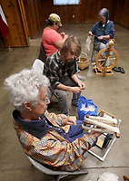 NWA Democrat-Gazette/DAVID GOTTSCHALK   Caye Mott (from bottom) uses a niddy noddy to wrap yarn Wednesday, May 3, 2017, during a a Spin-A-Round meeting of the Wool and Wheel Handspinners with Harrison McNeill, Kristy Casamayor and Kathleen McGill in the Latta Barn at Prairie Grove Battlefield State Park. The group meets every first Wednesday of the month at the park and every third Saturday at Ozark Folkways in Winslow. The group is open to the public and invites participation and observation.