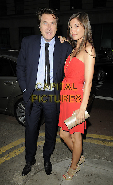 BRYAN FERRY & AMANDA SHEPPARD.At the Louis Vuitton  Maison store opening dinner party, New Oxford Street, London, England, UK, May 25th 2010..full length blue shirt black tie suit strapless red dress gold clutch bag open toe beige shoes .CAP/CAN.©Can Nguyen/Capital Pictures.