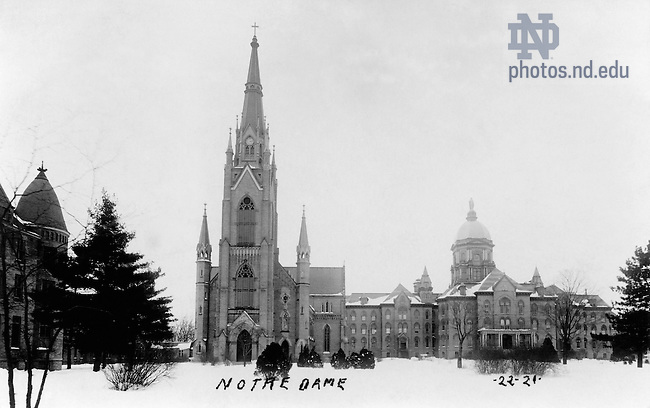 GFCL 48/62:  Postcard of Main Quad with Sorin Hall, Basilica of the Sacred Heart, and Main Building in winter with snow, c1921-1922..Image from the University of Notre Dame Archives.