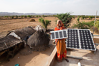 Santosh Devi, aged 19, poses for a portrait on the rooftop with her solar panels. She graduated 2 years ago from the solar engineering course of the Barefoot College in Tilonia, Ajmer, Rajasthan, India. She has since solar powered 20 homes in her village, Balaji Ki Dhani, Bauli, Nagur District, Rajasthan, making it the first village in India to be 100% solar powered in all houses. Above this, she does all maintenance for the neighbouring village, Gudda Ki Dhani, where the previous male solar engineer had left the village to find unrelated work in the city. Barefoot College prefers training women to be solar engineers for this reason that they have higher chances of staying in the village instead of moving to the cities. Photo by Suzanne Lee for Panos London