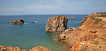 Coastal stacks and stumps orange coloured crumbling  cliffs rise from Atlantic Ocean at Cabo de São Vicente, Cape St Vincent, Algarve, Portugal, southern Europe