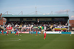 Supporters watching the early action at the Mersey Travel Arena, home to Marine Football Club (in white), as they played host to Ilkeston FC in a Northern Premier League premier division match. The match was won by the home side by 3 goals to 1 and was watched by a crowd of 398. Marine are baed in Crosby, Merseyside and have played at Rossett Park (now the Mersey Travel Arena)  since 1903, the club having been formed in 1894.