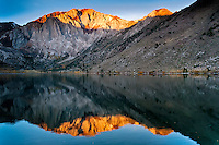 First brilliant rays of sunshine on the highest peaks reflecting on Convict Lake