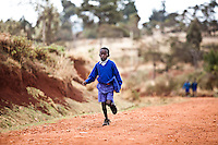 A Kenyan schoolboy runs to school on a dirt road in Iten, Kenya.