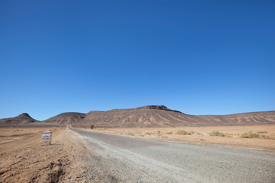 Desert landscape with street and mountains against clear blue sky near Tagounite, Sahara desert, Morocco.