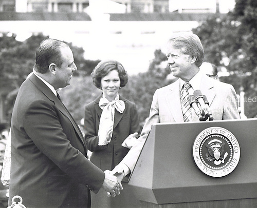 United States President Jimmy Carter, right, and Prime Minister Raymond Barre of France, left, shake hands at the conclusion of the the full honor arrival ceremony on the South Lawn of the White House in Washington, DC on September 15, 1977.  Prime Minister Barre is in Washington for two days of talks with top officials in the Carter Administration.  First lady Rosalynn Carter, center, applauds. <br /> Credit: Arnie Sachs / CNP
