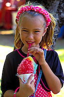 Young girl eating a rainbow shave ice treat
