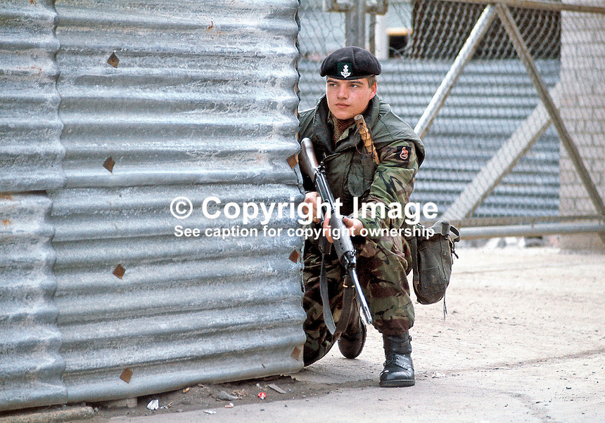 Soldier on foot patrol crouches with his rifle in Belfast, N Ireland, UK. Ref: 19710910003 (Linenhall 431/71/Neg 6a.<br />