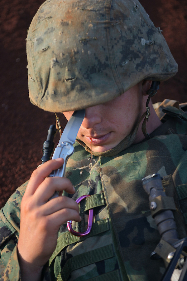 With a knife in hand, a sprig of grass in his teeth, and a lucky purple carabine clipped to his flak jacket,  LCpl. Prasch (Bravo Co. 1/4 Marines) - a mortician turned Marine - placidly awaits the detonation of a C-4 shaped-charge behind a protective berm at the Schofield Army Barracks demolition range.<br />