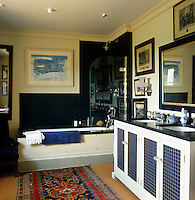 The walls of this masculine blue and white bathroom are lined with old prints and photographs