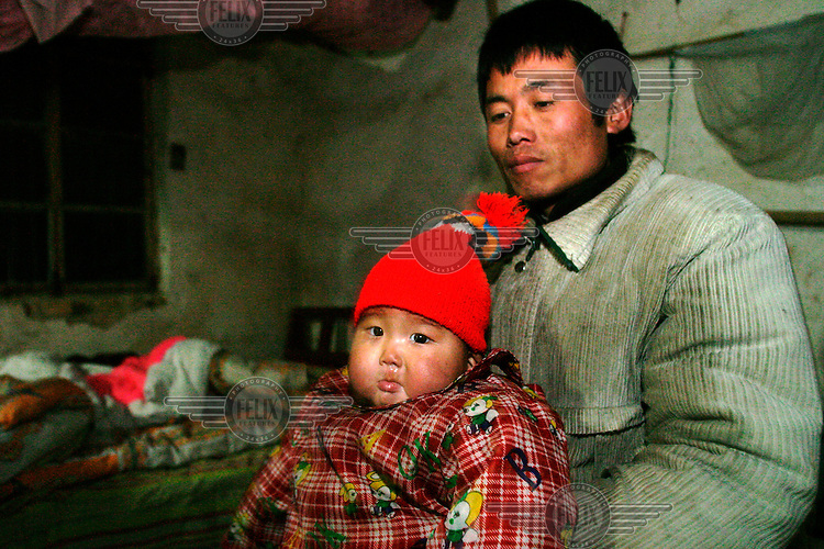HIV positive 33 year old Nie Xiangdong holds his youngest son, one year old Nie Saner, who is also HIV positive, at their dilapidated home. The baby contracted the HIV virus from his mother Chen Hongyin, who like Nie Xiangdong and her parents, contracted the disease when she sold blood at unregulated but government sanctioned blood centres during the early 1990s. Six out of eight residents of the Nie household are HIV positive.