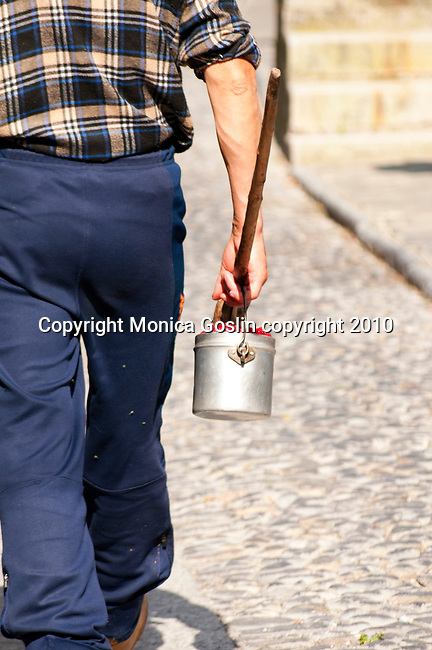 A man carries a small pail of fresh rasberries through the town of Bene Lario in a valley just near Lake Como, Italy
