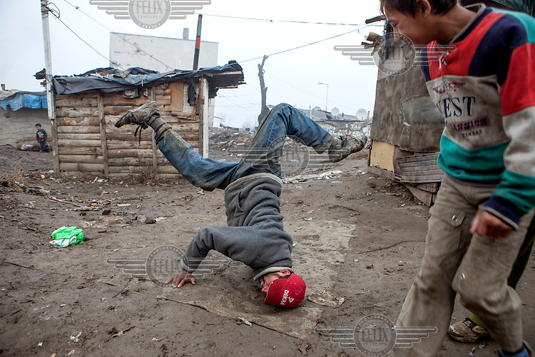A young man showing his break dance skills on a muddy patch of ground in the middle of the Roma settlement located in 'Budulovskej Street'.