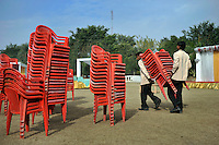 Workers carry stacks of chairs at Grewal Farms, one of many wedding reception centres in Amritsar which employs hundreds of staff during the wedding season to work around the clock hosting day and night marriage ceremonies and parties.