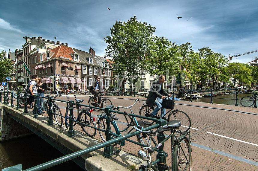 Bikers riding over the bridge in Amsterdam