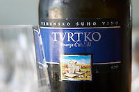 Wine glasses in the tasting room. Bottle of Tvrtko Vrhunsko Suho Vino white wine. Detail of label with a picture of a monument and vineyard. Vinarija Citluk winery in Citluk near Mostar, part of Hercegovina Vino, Mostar. Federation Bosne i Hercegovine. Bosnia Herzegovina, Europe.