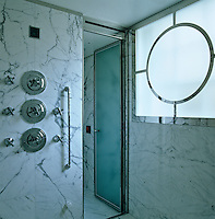 The wet room is a walk-in shower which is lined with white marble