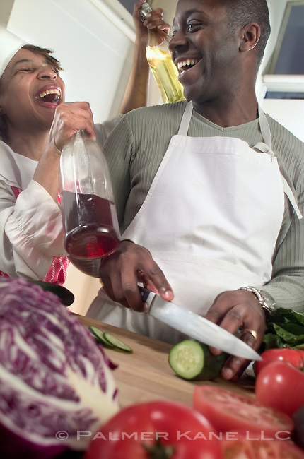 African American couple preparing salad in kitchen at home