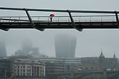 A woman with a pink umbrella crosses the Thames Millenium Bridge in heavy mist.