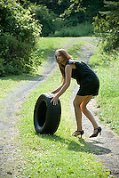 Young woman pushing tire up hill