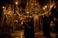 Mount Athos - The Holy Mountain.<br /> A monk lights candles during a midnight vigil. Monks usually pray in the early hours of the morning as they believe this is when they are closer to God and their prayers can be heard. <br /> <br /> Photographer: Rick Findler