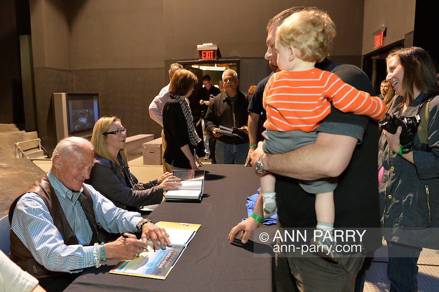 "May 11, 2013 - Garden City, New York U.S. -  Astronaut BUZZ ALDRIN, the second person to walk on the moon, signs his new illustrated history of space exploration ""Look to the Stars"" for a toddler boy, at the book signing for that and Aldrin's other new book ""Mission to Mars.""  After Aldrin, the NASA astronaut engineer of Apollo 11 in 1969, gave a Sold Out lecture, people who bought his books at the museum book store could attend the book signing in the Cradle of Aviations Museum's LEM room."