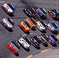 NASCAR driver Jeff Gordon leads a pack of cars through turn four at Talladega, AL enroute to vicory in the Diehard 500 at Talladega Superspeedway 4/16/00. (Photo by Brian Cleary)