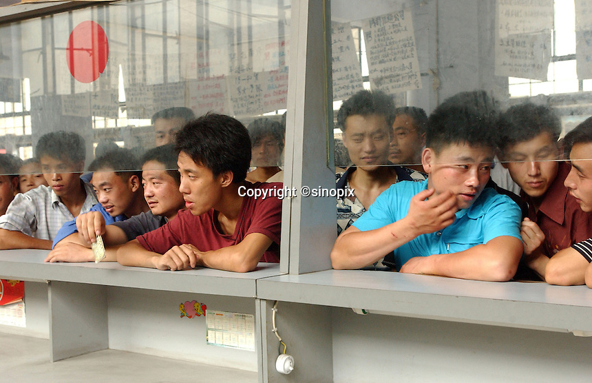 Unemployed workers wait at the window of Chengdu's labour market as the officers eat their lunch.  The labour market is one of China's largest and attracts peasants from the surrounding Sichuan country-side..17-JUL-02
