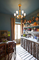 In the kitchen the chandelier and chairs are Art Deco designs and the copper pans hanging from the rail were bought from a sale at the Hotel Monceau in Paris