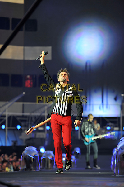 Matt Bellamy of Muse.Muse perform live in concert, Emirates Stadium, London, England, UK,.25th May 2013..music gig on stage performance performing full length red trousers guitar  arm raised up microphone  black white top jacket .CAP/MAR.© Martin Harris/Capital Pictures.