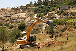 An Israeli bulldozer uproots Palestinian olive trees during the construction of Israel's controversial West Bank barrier in the village of Al Walaja near Bethlehem on 08-06-2010.