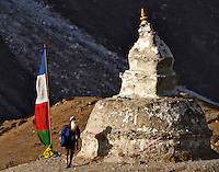 A trekker hikes by an old chorten (sherpa memorial) in the Khumbu Valley above the village of Dingboche, Nepal.