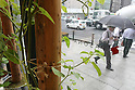 July 12, 2010 - Tokyo, Japan - People walking in the street are pictured through a window of the 'Urban Farm Pasona Group Headquaters' in Tokyo, Japan, on July 12, 2010. Aiming for an amicable working environment with 'Symbiosus with Nature' as a concept, more than 200 types of fruits and vegetables grow in the nine-floor building's verandas.