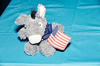 "A stuffed donkey toy holding an American flag and wearing a shirt reading ""Democracy in Action"" is seen on a table as Democratic presidential candidate and Congressional Representative Eric Swalwell (D-CA 15th) speaks at the Milford Democrats' Potluck Supper at the Unitarian Universalist Congregation Church in Milford, New Hampshire, USA, on Sat., Apr. 6, 2019. Swalwell is running primarily on gun control issues."