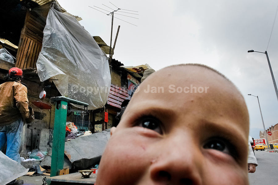 A Colombian boy hangs out in the 'Invasión', a temporary slum in Bogota, Colombia, 1 April 2006. The internal armed conflict in Colombia together with lack of social network caused appearence of small invasion slums in all Colombian urban zones in last years. These illegal settlements rise quickly in free uncontrolled spaces between industrial buildings, both in the city centres and peripheries. Shacks do not have sanitation network, neither electricity. Most of their inhabitants are war fugitives violently displaced from their original lands in the country by guerrilla or paramilitary forces. Picking up the rubbish and recycling it is a common survive strategy for people living in these temporal ghettos until those are not dismantled by city administration.