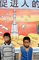 "China. Province of Henan. Village Xiaotan. Portrait of two young boys standing near a poster of a chinese space-rocket. The meaning of the poster is: "" practising family planning: promoting the all-round development of people"". It is a confirmation of the strength of chinese science on future developments in towns, education and space-rocket. © 2004 Didier Ruef"